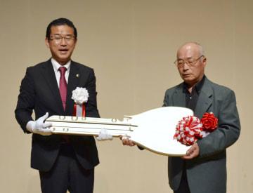 災害公営住宅が完成し開かれた式典で、山田司郎名取市長(左)から鍵のレプリカを受け取る入居者代表=8日午前、宮城県名取市