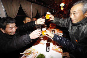 平賀駅を出発し、乾杯して宴会を楽しむ人たちでにぎわった忘年列車=7日午後6時半