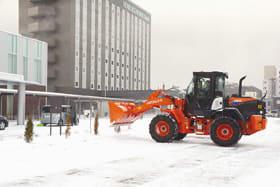 市生涯学習センター「きらん」の駐車場で雪を取り除く除雪車=8日午前8時ごろ、室蘭市中島町