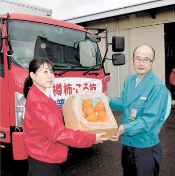 郵便局員(左)から樽柿を受け取る第1便のドライバー