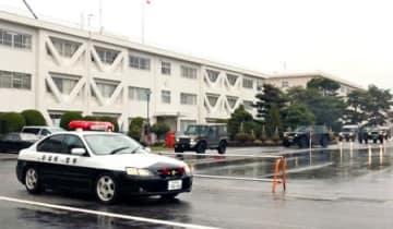 列を組んで走行する警察車両と、高機動車などの自衛隊車両=7日、新発田市