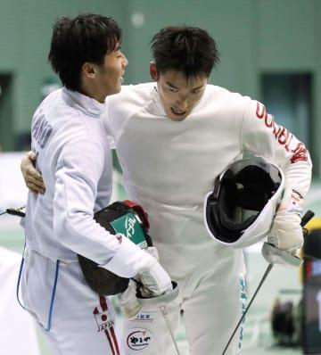 男子エペ個人で決勝進出を決め、加納虹輝(左)と健闘をたたえ合う見延和靖=駒沢体育館