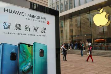 上海のアップルストア(右)の前に掲示された華為技術(ファーウェイ)の広告=10月、上海(ロイター=共同)