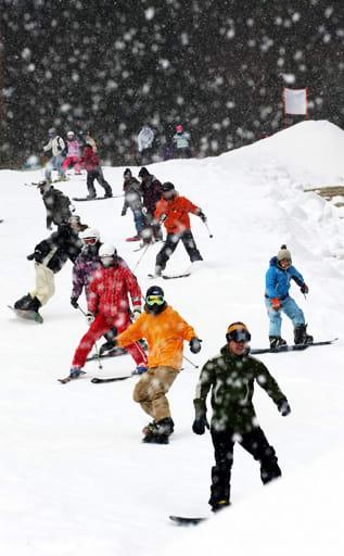 雪が舞うゲレンデでスキーやスノーボードを楽しむ来場者=8日午前10時23分、めがひらスキー場