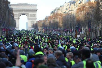 8日、パリのシャンゼリゼ大通りで黄色いベストを着て抗議する人々(ゲッティ=共同)