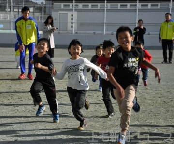 元気よく走る子どもたちと、指導する札場さん(左)