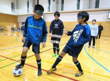 日本代表の加賀美和子さん(中央)に教わりながら、ブラインドサッカーを楽しむ小学生ら =逗子市逗子