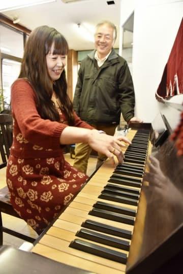 完成した竹製鍵盤のピアノを演奏する升崎直美さん(左)と笠島豊さん=福井県鯖江市の「鯖江工芸」