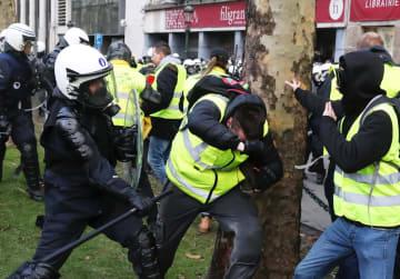8日、ベルギー・ブリュッセルで警官隊と衝突する、黄色いベストを着たデモ参加者(ロイター=共同)
