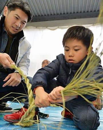 熱心に稲わらをねじる参加者(右)=8日、大阪市城東区の若宮八幡大神宮