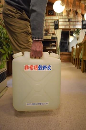 水道供給停止に備えてためた飲料水を運ぶペンションの経営者=8日、雫石町長山岩手山