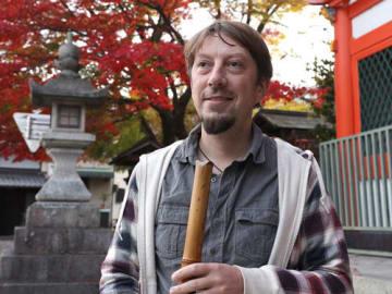 長等神社前で尺八を手にするセバスチャンさん。修験道にも関心が高く大峰山も訪れた(大津市三井寺町)