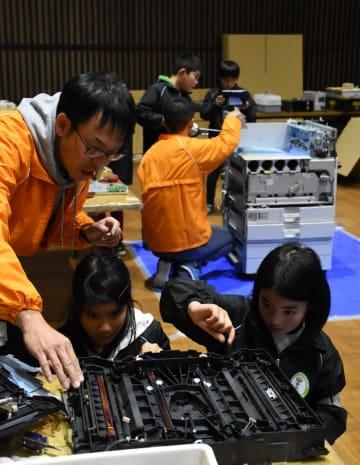 コピー機を分解して仕組みを学ぶ子どもたち=神埼市中央公民館