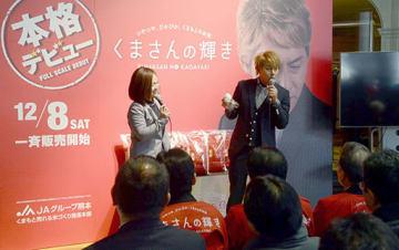 「くまさんの輝き」のおにぎりを食べながら、おいしさをPRするお笑い芸人のヒロシさん(中央右)=熊本市中央区