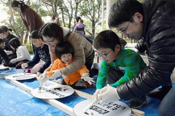 緑色の看板に置かれた型紙の上から、白いペンキを塗る子どもたち=熊本市東区