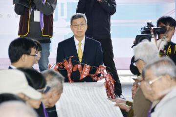 台湾の過去の政治犯の判決を取り消す式典に出席した陳建仁副総統(中央)と、被害者の名前を記した紙を囲む関係者=9日、新北市内(共同)