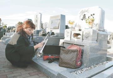 亜樹さんの誕生日に墓参し、遺品のトランペットを見詰めるみゆきさん。月命日と2人の誕生日には必ず訪れるという