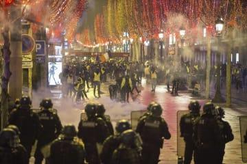 8日、パリの通りで対峙する警官隊とデモ参加者(アナトリア通信提供・ゲッティ=共同)
