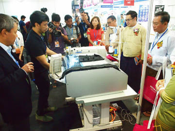 JUKIのブースで展示されたベルトループの自動縫製機に見入るミャンマーの政府、業界関係者=6日、ヤンゴン