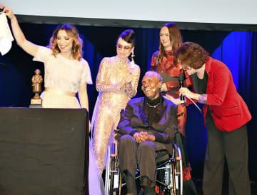 ストックホルムで開かれた市民文学賞の授賞式に車いすで出席する、受賞者のマリーズ・コンデさん(中央)=9日(共同)