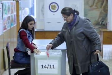 9日、アルメニアの首都エレバンで議会総選挙の投票をする女性(タス=共同)