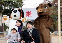 来年は良い年に-。願いを込め、干支の着ぐるみと記念撮影をする家族連れら=神戸市灘区王子町3