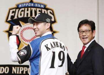 日本ハムの入団記者会見で、背番号「19」を披露する金子弌大投手。右は栗山監督=10日午後、札幌市内のホテル