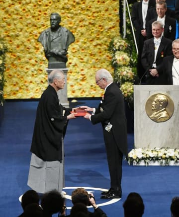 ノーベル賞授賞式で、スウェーデン国王カール16世グスタフ(右)から医学生理学賞のメダルと賞状を受け取る本庶佑・京都大特別教授=10日、ストックホルムのコンサートホール(共同)