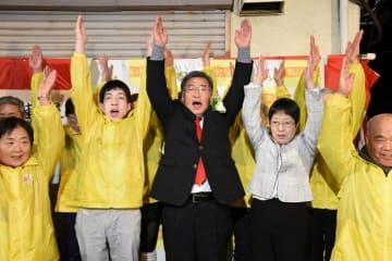 大井町長選で初当選を決め、支持者と万歳する小田真一氏(中央)=9日午後10時20分ごろ、同町金子の選挙事務所