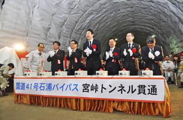 発破セレモニーでボタンを押し宮峠トンネル貫通を祝った出席者ら=高山市久々野町山梨