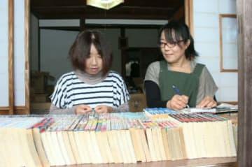集まった漫画本にラベルを貼って分類するメンバー=豊後高田市田染真中の「蔵人」