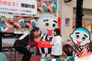 【廣田代表(左)から感謝状を受け取り、笑顔を見せる女の子=四日市市の諏訪栄町で】