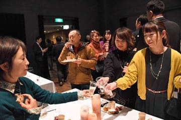 リンゴ酒で乾杯する来場者たち