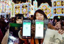 ペイペイでルミナリエの公式グッズを購入した来場者。スマートフォンには支払額が表示される=10日夜、神戸市中央区、東遊園地(撮影・後藤亮平)