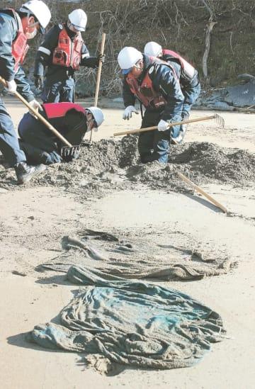 砂に埋まった衣類を掘り出す署員