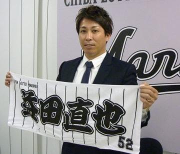 契約更改交渉を終え、グッズを持ってポーズをとるロッテの益田直也投手=11日、千葉市のZOZOマリンスタジアム