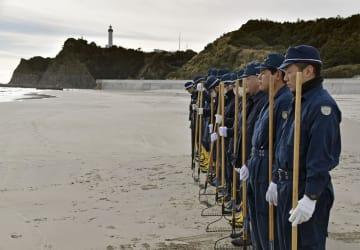 福島県いわき市の海水浴場で、捜索前に黙とうする警察官=11日午前
