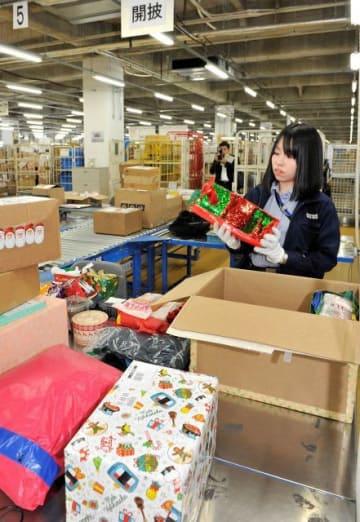 海外からクリスマスプレゼントが入った小包を検査する税関職員=川崎市川崎区の横浜税関川崎外郵出張所