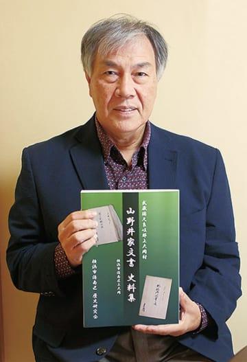史料集を手にする田上名誉教授
