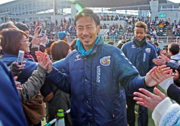 ファンらと笑顔でタッチする前田=長崎市営ラグビー・サッカー場