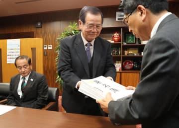 天神ダムへのカヌー競技場誘致を求める署名を手渡す長友田野町商工会副会長(中央)=11日午後、宮崎市役所
