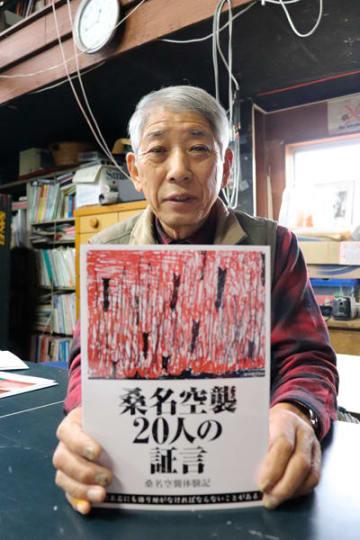 【桑名空襲の体験記を手にする加藤さん=桑名市内で】