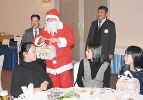 サンタクロースからクリスマスプレゼントを受け取る子どもたち