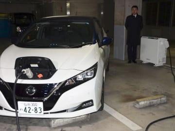 東北電などが電力需給調整を実証試験中の充放電スタンド(右)と電気自動車