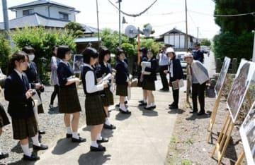 修学旅行で益城町を訪れ、地震直後の写真パネルなどを見学する東京の高校生たち=5月