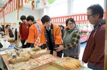 東高マーケットで客(右の2人)に商品の説明をする八代東高の生徒=八代市