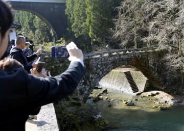 SNS講習会で、アーチ部分と影がハート型をつくる二俣橋を撮影する自治体の担当者ら=美里町
