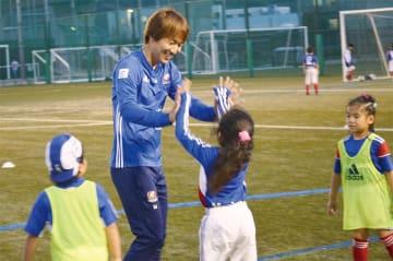 ゴールを決めハイタッチするスクールの児童と天野選手