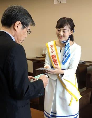 高井盛雄副知事(左)に宝くじを手渡す「幸運の女神」の矢吹真穂さん=11日、県庁