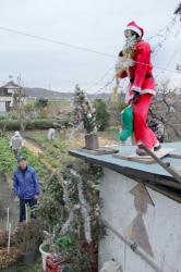 サンタクロースの格好をしたかかしを見上げる小西さん(東近江市山上町)